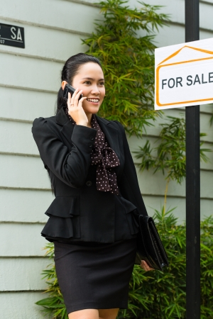 accommodation broker: Real estate - Young Indonesian real estate showing an house or apartment, it could be the landlord too, she has a customer conversation with a prospective customer on the mobile phone