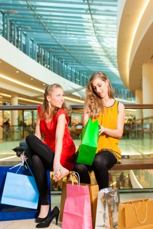 Two female friends with shopping bags having fun while shopping in a mall, the feet hurt already photo