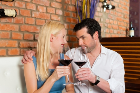 Attractive young couple drinking red wine in restaurant or bar photo