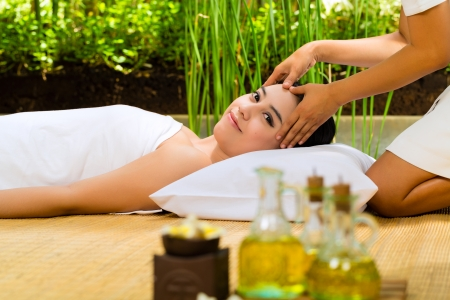Beautiful Asian woman having a wellness Head massage in a tropical setting and feeling visibly good about it Stock Photo - 24433496