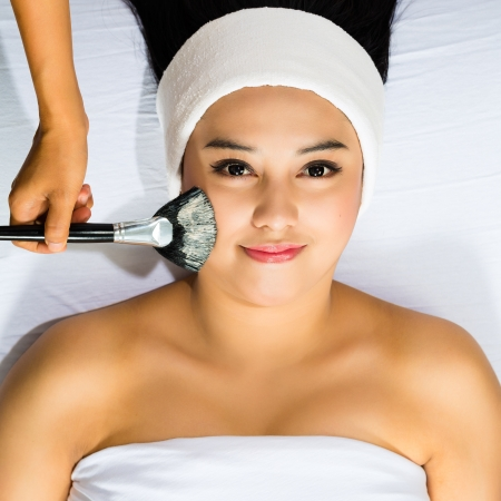 Young Asian Woman having a mask or cream applied in the course of a beauty treatment photo