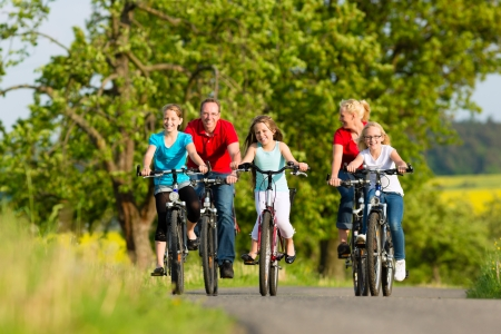 dirt bikes: Family with three girls having a weekend excursion on their bikes or bicycles on a summer day in beautiful landscape