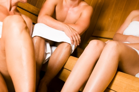 Three people  one male, two female  enjoying a hot sauna, having a casual chat photo