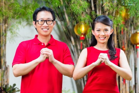 china people: Couple celebrating Chinese new year traditional greeting, wearing red