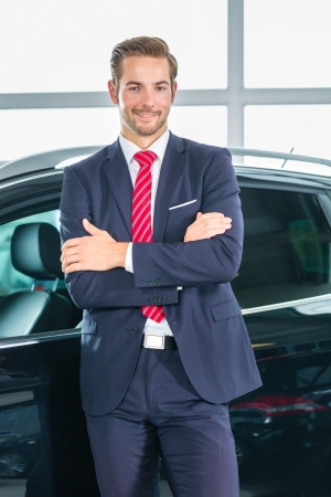Seller or car salesman in car dealership presenting his new and used cars in the showroom photo