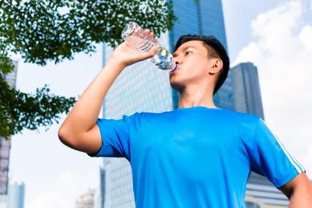 tomando agua: Deportes urbanos - hombre indonesia asi�tica haciendo gimnasio en la ciudad en un hermoso d�a de verano