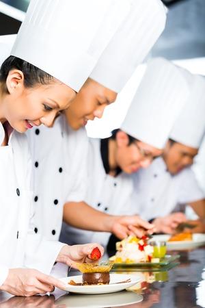 k�che: Asian indonesischen Koch zusammen mit anderen K�chen im Restaurant oder Hotelk�che kochen, Finishing Teller oder Platte zum Dessert Lizenzfreie Bilder
