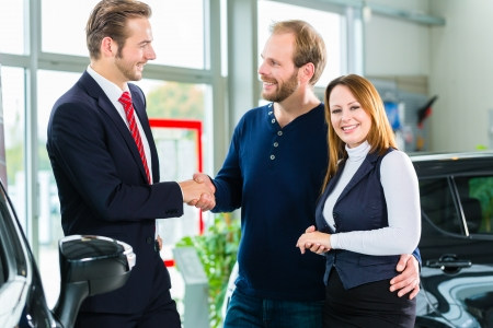 Seller or car salesman and clients or customers in auto dealership presenting the interior decoration of new and used cars at showroom photo