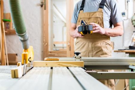 Timmerman die aan een elektrische cirkelzaag te snijden boards Stockfoto