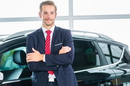 Vendeur ou vendeur de voiture au concessionnaire automobile présentant ses voitures neuves et d'occasion dans la salle d'exposition