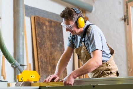 Carpenter working on an electric buzz saw cutting some boards, he is wearing safety glasses and hearing protection for safe workplace photo