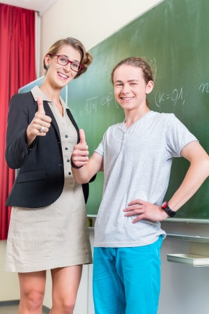 thump: School class Teacher and student stand in front of a blackboard with math work in a classroom during lesson Stock Photo
