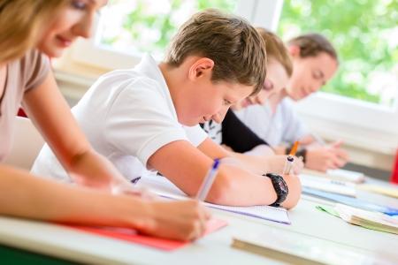Los estudiantes o los alumnos de la clase de escuela que escriben un examen de la prueba en el aula para concentrarse en su trabajo