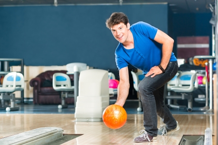 on strike: Young man in bowling alley having fun, the sporty man playing a bowling ball in front of the tenpin alley