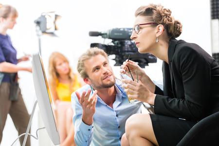 filmacion: Equipo o Director de discutir durante un descanso de la dirección de escena en el set de una producción de vídeo comercial o reportaje en una pantalla Foto de archivo