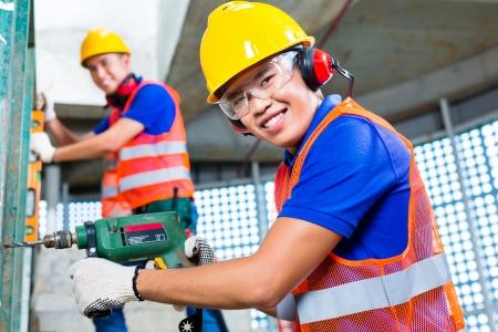 supervisores: Trabajadores de la construcción en Indonesia Asia perforación con una máquina o un taladro, nivel de burbuja, protección para los oídos, guantes y casco de seguridad o el casco en una pared de un edificio torre Foto de archivo