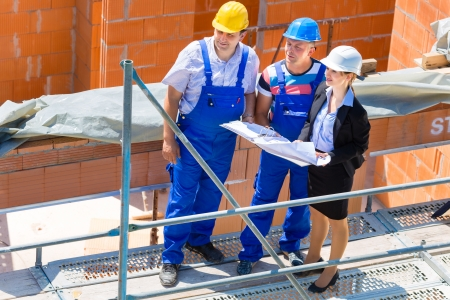 Construction site Team or architect and builder or worker with helmets discuss on a scaffold construction plan or blueprint or checklist  photo