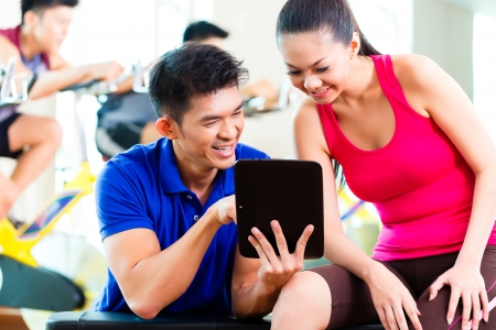 gymnasium: Asian Chinese Woman and personal fitness trainer in gym discussing training schedule and goals for workout