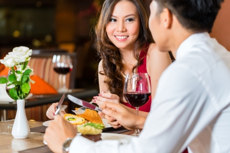 flirting women: Asian Chinese couple - Man and woman - or lovers flirting and having a date or romantic dinner in a fancy restaurant  Stock Photo