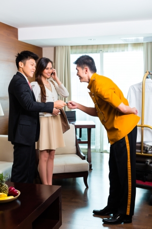 man in suite: Baggage porter or bellboy or page receiving tip for delivering the suitcase of guests to the hotel room or suite
