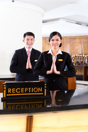 front desk: Chinese Asian reception team at luxury hotel front desk welcoming guests with typical gesture, a sign of good service and hospitality