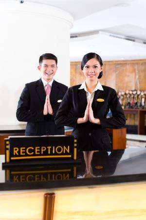 Chinese Aziatische receptie team bij de luxe hotel receptie verwelkomt gasten met typische gebaar, een teken van goede service en gastvrijheid