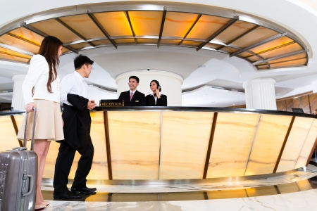 Asian Chinese woman and man arriving at front desk or reception of luxury hotel in business clothes with trolley  Banco de Imagens
