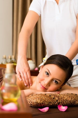 oriental massage: Chinese Asian woman in wellness beauty spa having aroma therapy massage with essential oil, looking relaxed