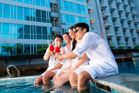 luxurious lifestyle: Two young and handsome Asian Chinese couples or friends drinking cocktails in a luxurious and fancy hotel pool bar
