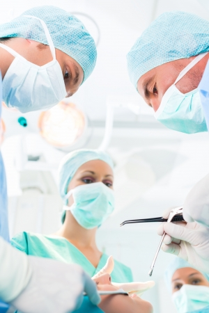 Hospital - surgery team in operating room or Op of a clinic operating on a patient in an emergency situation photo