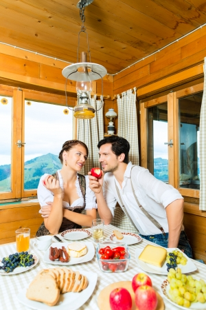 hunter's cabin: Couple in a traditional mountain hut having a meal, breakfasting with fruits, cold cuts, cheese and bread Stock Photo