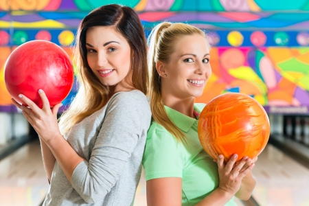 bowling alley: Young people or friends, man and women, playing bowling with a ball in front of the ten pin alley, they are a team Stock Photo