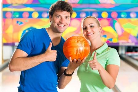 bolos: Joven pareja o amigos, hombre y mujer, jugando a los bolos con una bola en frente del callejón diez pines, que son un equipo