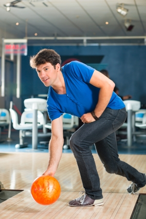 Young man in bowling alley having fun, the sporty man playing a bowling ball in front of the tenpin alley