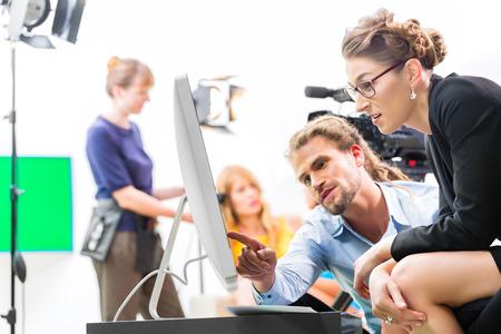 aziende: Squadra o regista discutere durante una pausa direzione scena sul set di una produzione video commerciale o reportage in uno schermo Archivio Fotografico