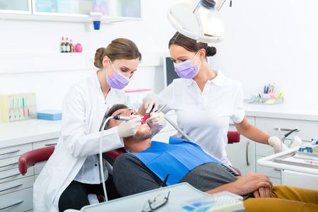 dentiste dans son cabinet ou au bureau le traitement des patients de sexe masculin avec assistants portant des masques et des gants Banque d'images