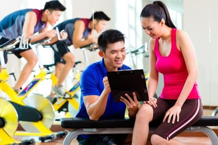 mujer china: Mujer china asi�tica y entrenador personal de fitness en el gimnasio de la discusi�n horario de entrenamiento y objetivos de entrenamiento