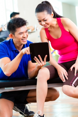 Asian Chinese Woman and personal fitness trainer in gym discussing training schedule and goals for workout  photo