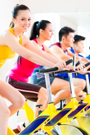 Chinese Asian sport group of men and women in fitness club or gym exercising on spinning bikes photo