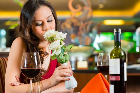 up date: Chinese nervous, hoping, lonely, dreamy, heartsick woman in a restaurant waiting for a date got stood up  Stock Photo