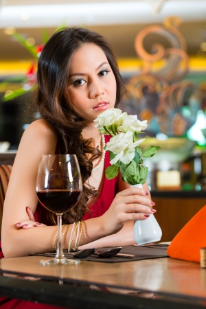 stood up: Chinese nervous, hoping, lonely, dreamy, heartsick woman in a restaurant waiting for a date got stood up  Stock Photo