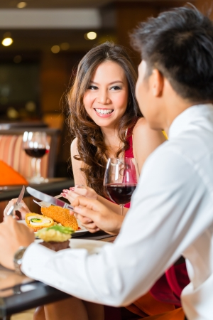 Asian Chinese couple - Man and woman - or lovers flirting and having a date or romantic dinner in a fancy restaurant  Stok Fotoğraf