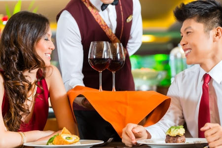 chinese dinner: Asian Chinese waiter or steward serving man and woman or couple red wine in glasses on a tray in fancy restaurant or hotel