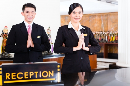 good service: Chinese Asian reception team at luxury hotel front desk welcoming guests with typical gesture, a sign of good service and hospitality