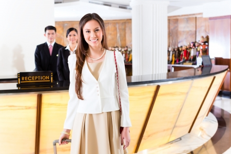 Asian Chinese woman arriving at front desk of luxury hotel in business clothes with trolley photo