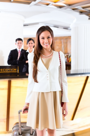 Asian Chinese woman arriving at front desk of luxury hotel in business clothes with trolley Stock Photo