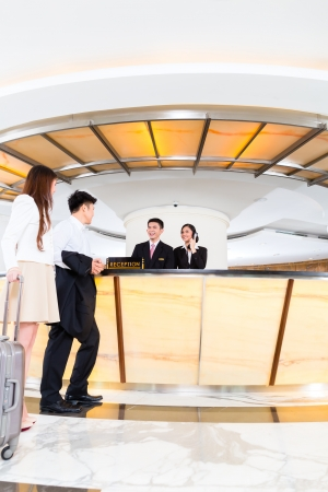 hotel receptionist: Asian Chinese woman and man arriving at front desk or reception of luxury hotel in business clothes with trolley  Stock Photo