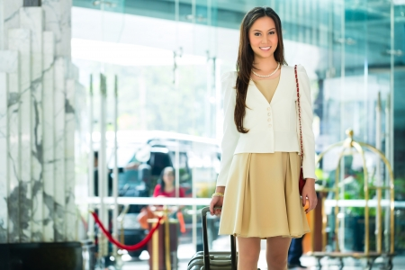 Asian Chinese woman arriving at luxury hotel in business clothes with trolley entering through a glass door into lobby Stock Photo
