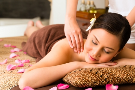back massage: Chinese Asian woman in wellness beauty spa having aroma therapy massage with essential oil, looking relaxed