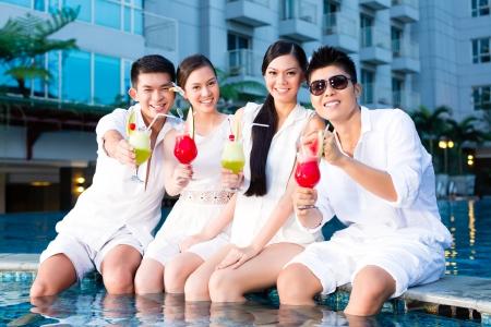 people partying: Two young and handsome Asian Chinese couples or friends drinking cocktails in a luxurious and fancy hotel pool bar